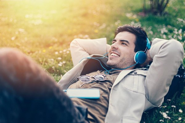 A man lying down and listening to music