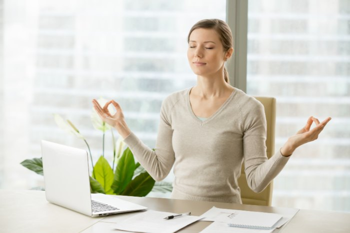 Image of a woman at work trying to relieve stress